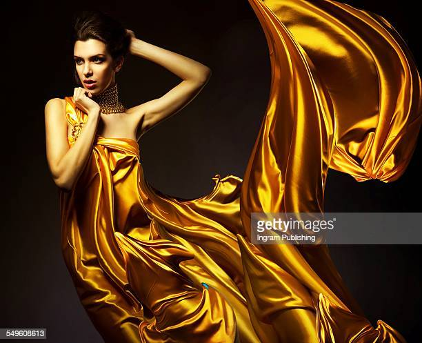 Woman wrapped in golden silk fabric