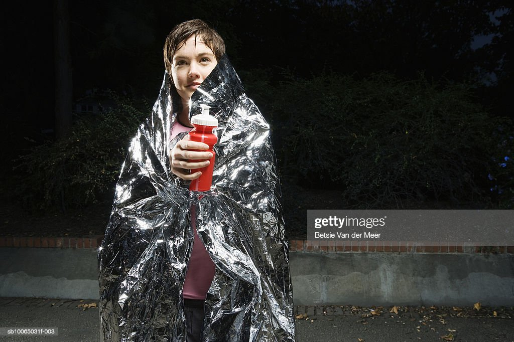Woman wrapped in silver survival blanket, looking up, smiling : Stock Photo