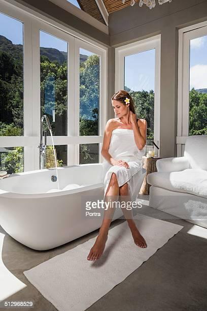 Woman wrapped in towel sitting on bathtub