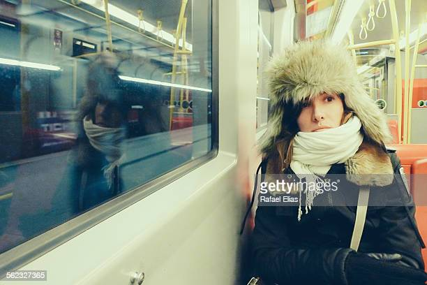 Woman wrapped up warm in winter clothes on subway