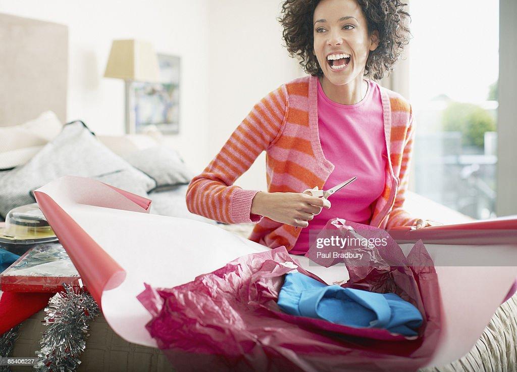 Woman wrapping Christmas gift : Stock Photo