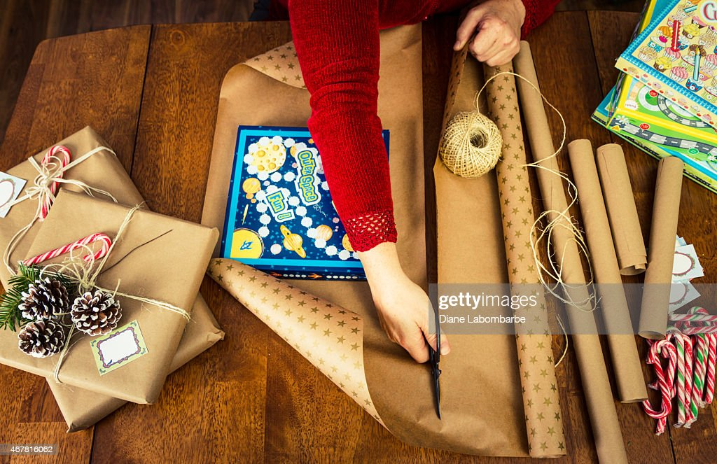 Woman Wrapping Christmas Gifts For Children From Above