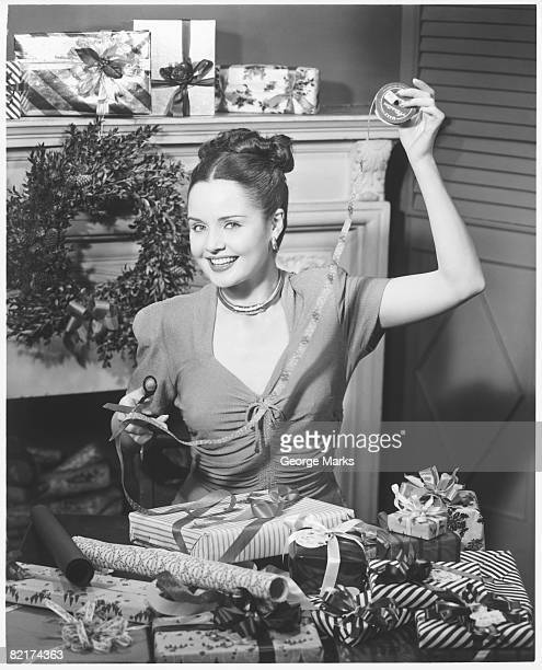 Woman wrapping Christmas presents in living room, (B&W), portrait