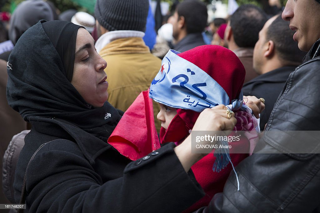 A woman wraps a banner around her childs head during a demonstration after the assassination of Chokri Belaid political opponent to the Tunisian government on February 9, 2013 in Tunis,Tunisia.