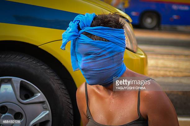 A woman wraps her face during a joint protest against a rise on public bus fares and the Brazil 2014 FIFA World Cup in Rio de Janeiro Brazil on...