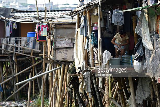 A woman wrings a cloth in a shanty house perched on stilts near the Pluit Dam area of North Jakarta Indonesia on Wednesday Nov 5 2014 Jakarta a...