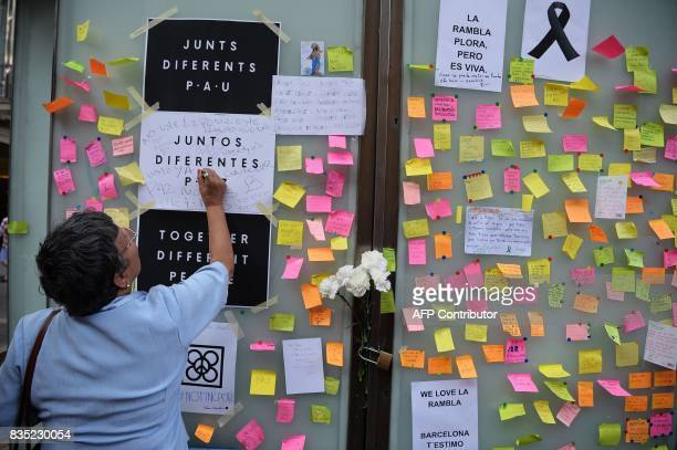 A woman writes a message against the attacks and for the victims of the attack in Barcelona on Las Ramblas boulevard in Barcelona as people pay...