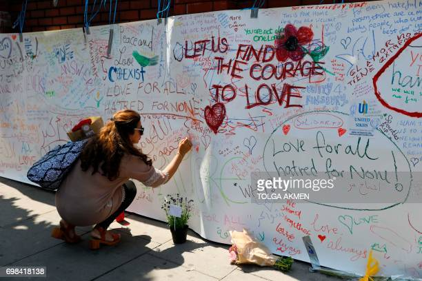 A woman writes a message on a banner hanging outside of Finsbury Park Mosque in the Finsbury Park area of north London on June 20 following a van...