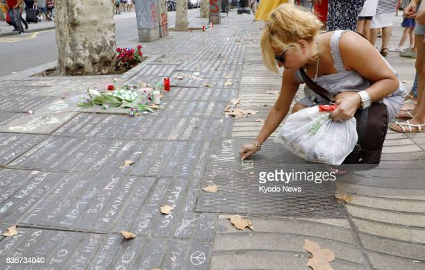 A woman writes a message on a street in Barcelona on Aug 19 where a terror attack occurred Spanish police suspect a total of 12 people were part of a...