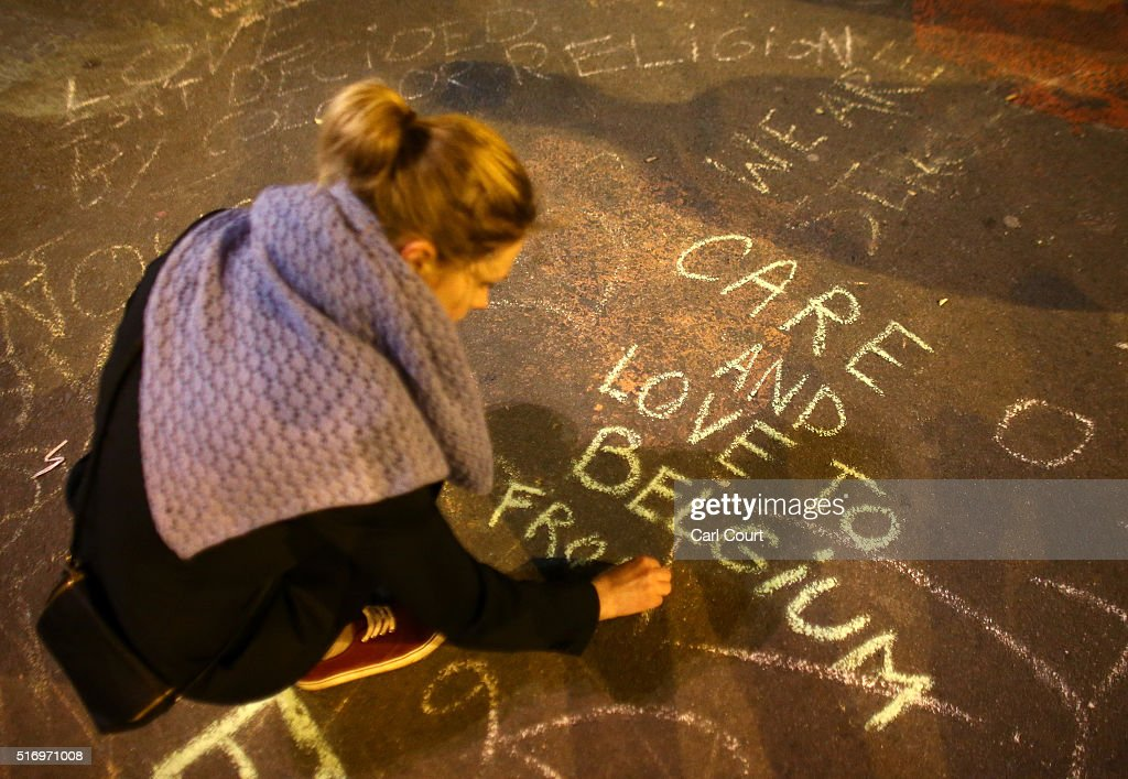 A woman writes a message on the ground as people leave tributes at the Place de la Bourse following today's attacks on March 22 2016 in Brussels...