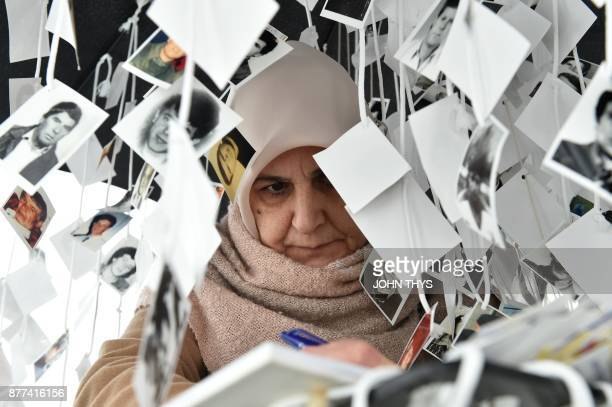 TOPSHOT A woman writes a note in the golden book inside the memorial of victims in front of the International Criminal Tribunal for the former...