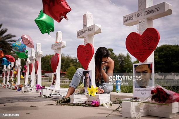 A woman writes a note on a cross for Eric Ivan OrtizRivera at a memorial with wooden crosses for each of the 49 victims of the Pulse Nightclub next...