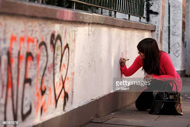 A woman writes a tribute to the Beatles on the wall outside the Abbey Road recording studios which have been put up for sale by their owner EMI on...