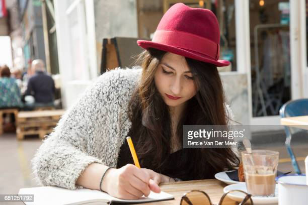 Woman writes in note book, sitting in outdoor cafe.