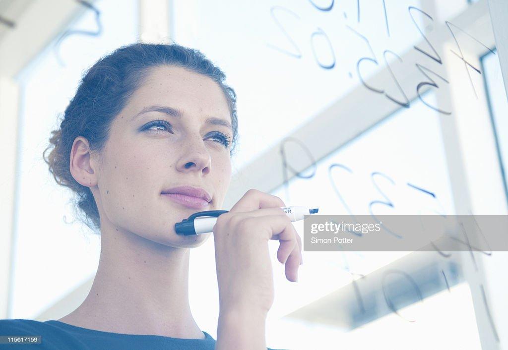 Woman writes on glass : Stock Photo