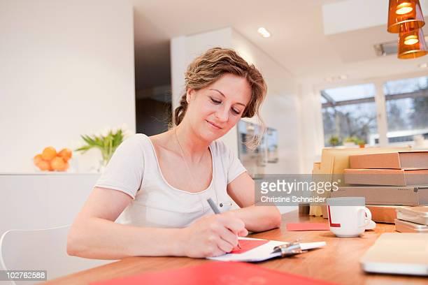 Woman writing address on an envelope