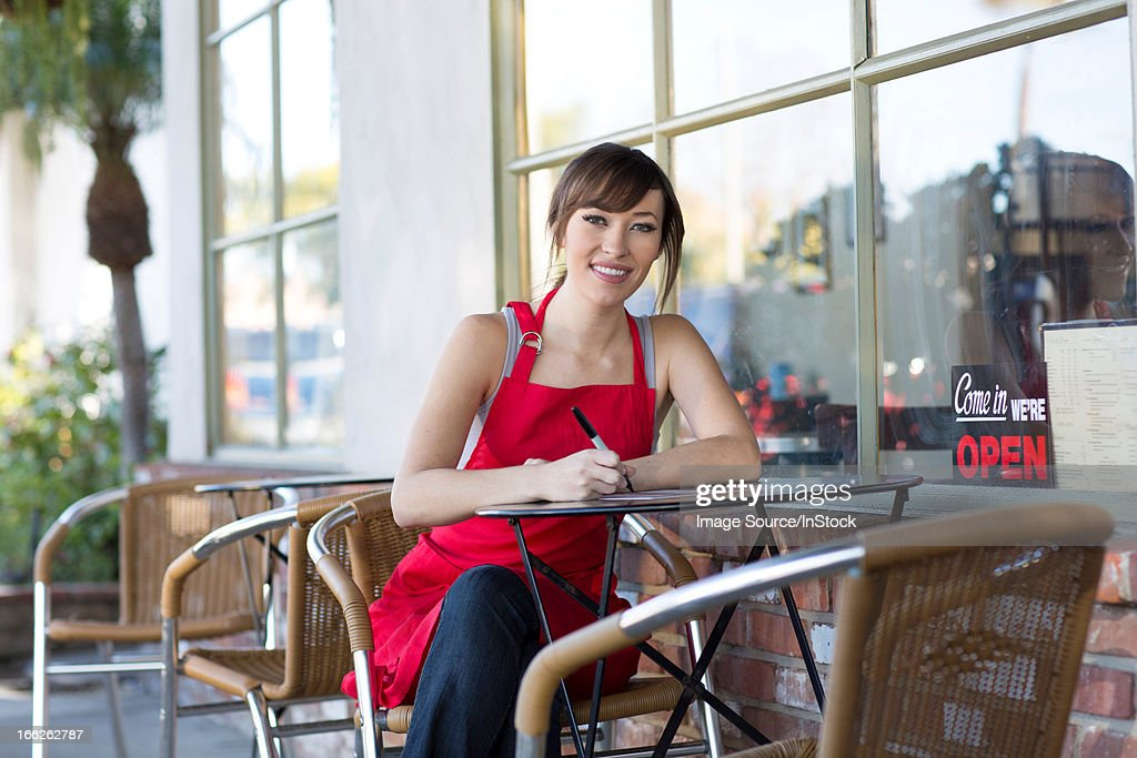 Woman writing at cafe table : Stock Photo