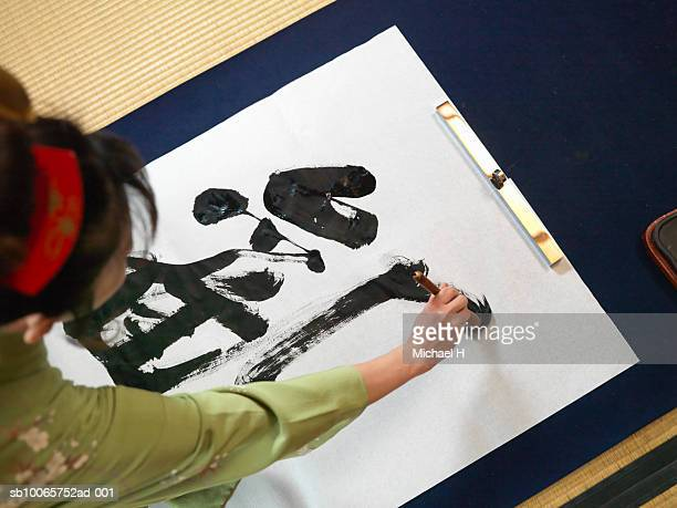 Woman writing calligraphy, high angle view