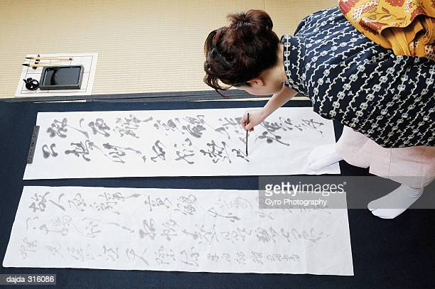 Woman writing characters in a Japanese paper