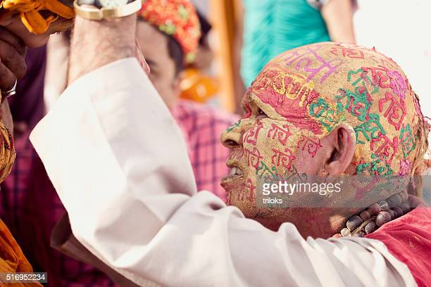 Woman writing 'Happy Holi' on man face in Hindi