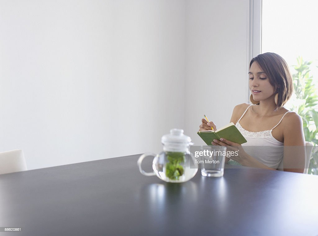 Woman writing in diary and drinking tea : Stock Photo