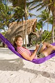 Woman writing in hammock on beach