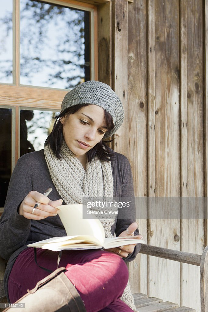 Woman writing in notebook on porch : Stock Photo