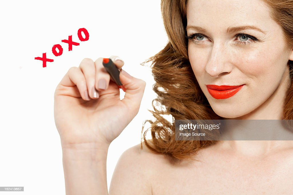 Woman writing kisses and hugs on glass with red lipstick : Stock Photo