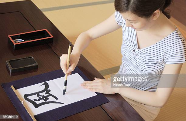 A woman writing letters with ink brush