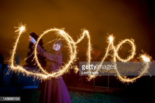 Woman writing LOVE with sparkler