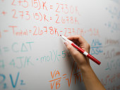 Woman writing mathematical equations on whiteboard, close-up