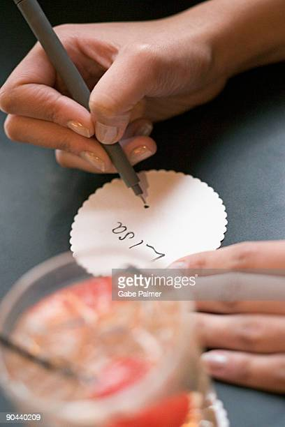 Woman writing name on paper coaster