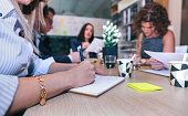 Close up of woman writing notes in a business meeting with teamwork sitting around of table in company headquarters