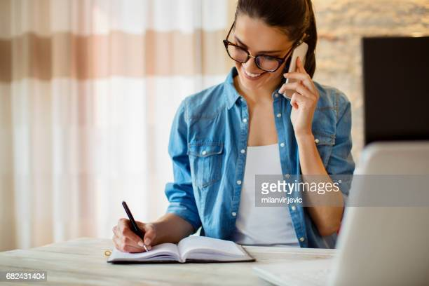 Woman writing notes in notebook