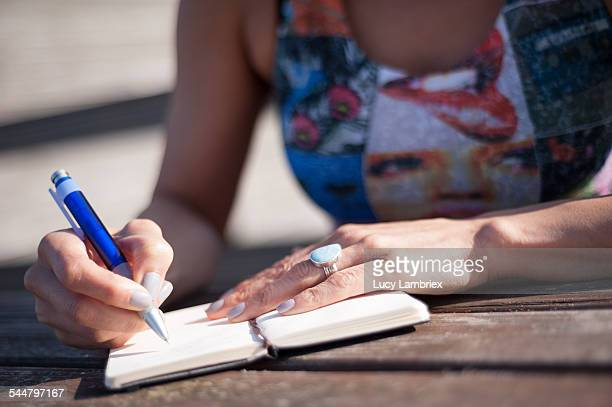 Woman writing notes outside