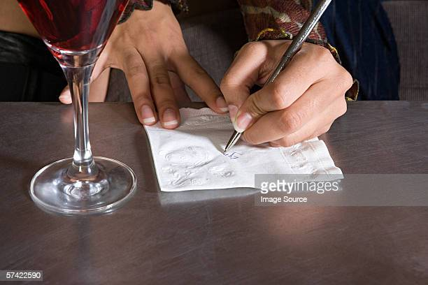 Woman writing on a napkin