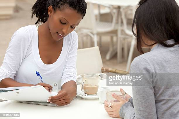 Woman writing on a notebook during a cafe meeting