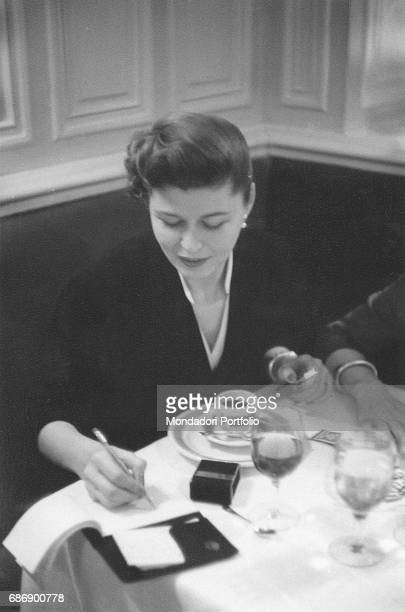 Woman writing on a notebook sitting in a caf' This picture is taken from the monography 'Mario De Biasi Il mio sogno Š qui' curated by Enrica Vigan•...