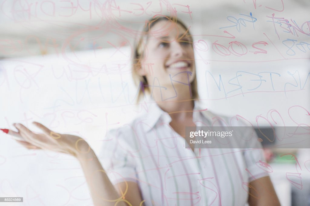Woman writing on glass wall, smiling : Stock Photo