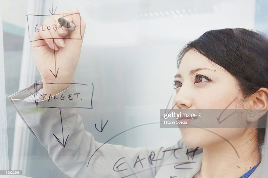 Woman writing on glass with marker pen : Stock Photo
