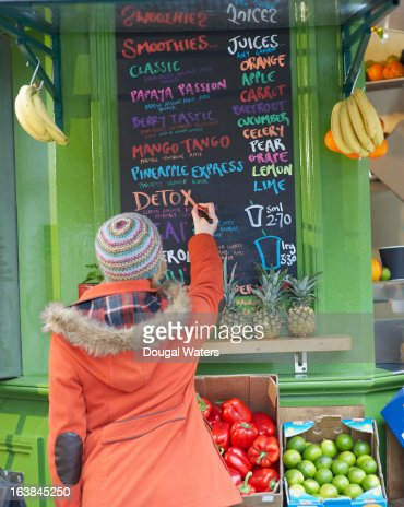 Woman writing on sign at juice bar. : Stock Photo