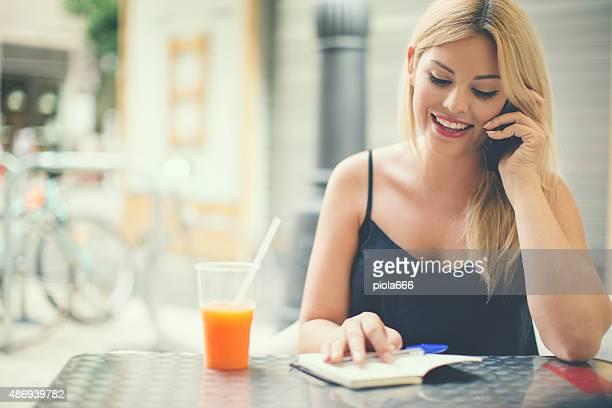 Femme écrit dans son agenda plans