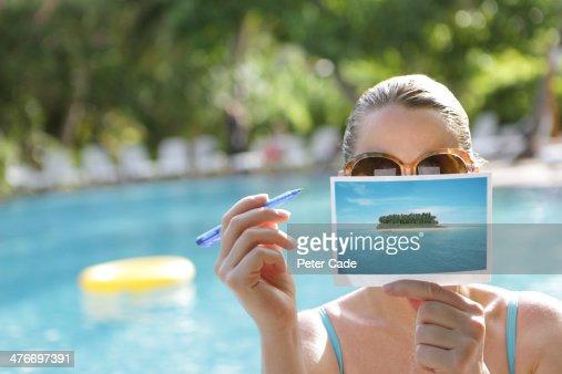 Woman writing postcard by swimming pool