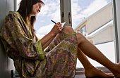 Woman writing postcard by window