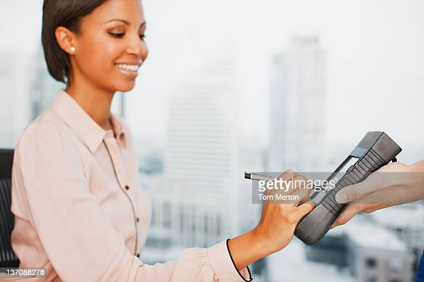Woman writing signature on electronic device