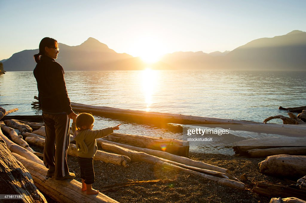 Woman w/small child pointing out to body of water at sunset : Stock Photo