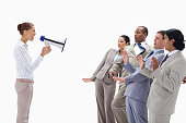 Woman yelling at business people through a megaphone against white background