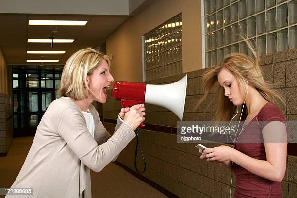 Woman yelling through a bullhorn at an unfazed teenage girl