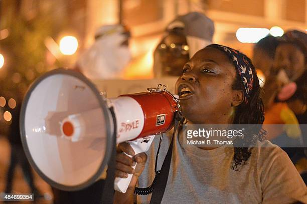 A woman yells at onlookers through a megaphone during a protest action through the Central West End of St Louis Missouri on August 20 2015 After a...