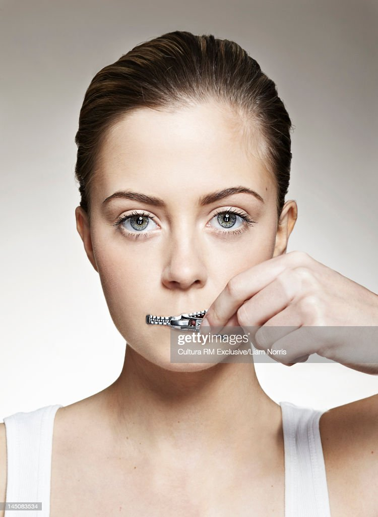 Woman zippering mouth closed : Stock Photo